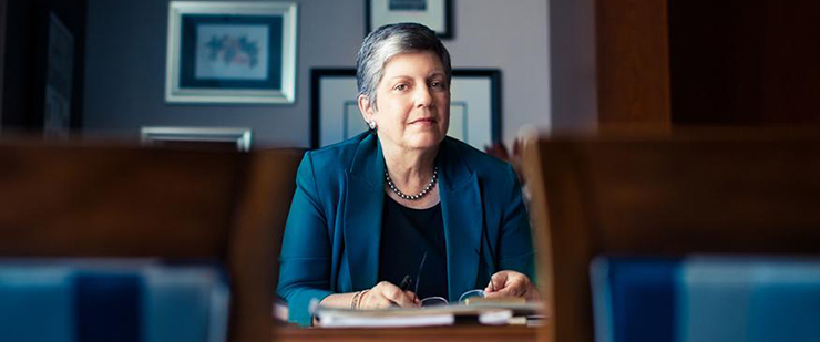 University of California President Janet Napolitano seated at her desk.